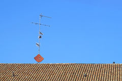 Antennas on the rooftops with a background of blue sky Stock Photos