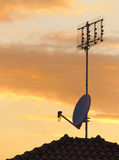 Antennas at sunset. A classic antenna and a satellite dish on a roof at sunset, with beautiful warm skycolors royalty free stock photography