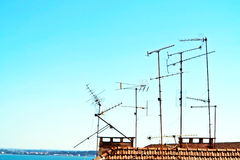 Antennas. Television antennas on the top of a building stock image