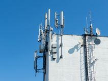 Antennas on top of a building. On a blue sky royalty free stock image