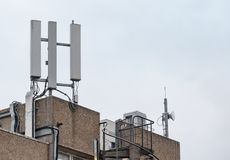 Roof top cellular communications and microwave antennas seen atop an office building. The antennas are used to supply a cellular 3G and 4G communications Royalty Free Stock Photo