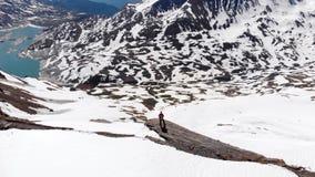 Antenne: über den Wanderer auf die schneebedeckte Gebirgsoberseite fliegen, Ski Bergsteigenschneeberg, Panoramablick bereisend au stock video footage
