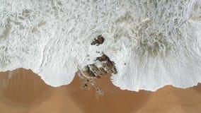 Antenne bewegt das Zusammenstoßen gegen Felsen auf sandigem Strand in Portugal wellenartig stock video