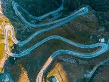 Antenne : complétez en bas du chaos de vue au-dessus de la route de montagne d'enroulement sur les Alpes italiens, le pré de croi Photos libres de droits