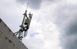 Antenne d'émetteur de téléphone portable sur le ciel avec beaucoup de nuages Images stock