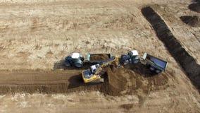 Antenne d'excavatrice chargeant le camion- sur un grand champ d'agriculture banque de vidéos