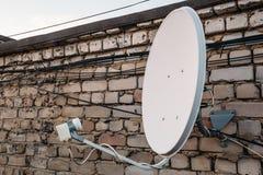 Antenne d'antenne parabolique sur le mur de briques au bâtiment Photo stock