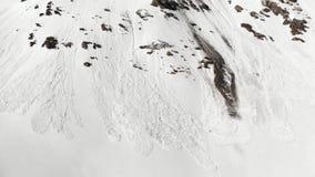 Antenne: das Fliegen nah an Schneelawine auf Gebirgsschneebedeckter Steigung deckt im Frühjahr auf stock video footage