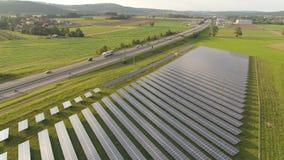 Antenne de bourdon d'une centrale solaire à côté de la route dans le paysage agricole banque de vidéos