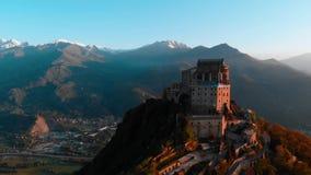 Antenne: de hommel die bij oude middeleeuwse abdij vliegen streek op bergbovenkant neer, sneeuwalpen als achtergrond bij zonsopga stock video
