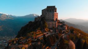 Antenne: de hommel die bij oude middeleeuwse abdij vliegen streek op bergbovenkant neer, sneeuwalpen als achtergrond bij zonsopga stock videobeelden