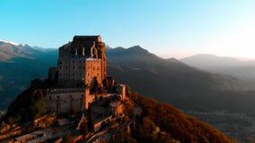 Antenne: de hommel die bij oude middeleeuwse abdij vliegen streek op bergbovenkant neer, sneeuwalpen als achtergrond bij zonsopga stock footage