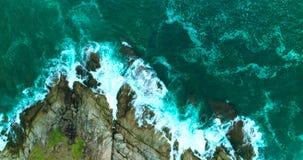 Antenne: De krachtige oceaangolven wassen omhoog grote rotsen stock videobeelden
