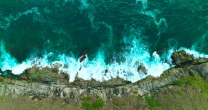 Antenne: De oceaangolven wassen omhoog grote rotsen op de overzeese rotsachtige kust stock footage