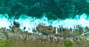 Antenne: De oceaangolven wassen omhoog grote rotsen op de overzeese rotsachtige kust stock video