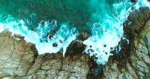 Antenne: De overzeese golven wassen omhoog grote rotsen stock footage