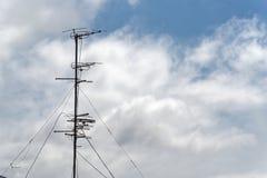 Antenne de télévision contre le ciel nuageux bleu image stock