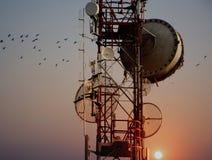 Antenne della torre di telecomunicazione con il tramonto Fotografia Stock