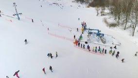 Antenne der Gruppe Skifahrer und Snowboarder, die auf Skiaufzug warten, um sie herauf die schneebedeckte Steigung zu reiten stock abbildung