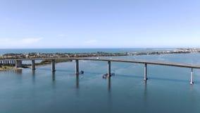 Antenne des Fliegens hinter einer Brücke in der Küstenstadt stock video