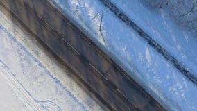 Antenne des sportifs courant sur le chemin neigeux près de la route urbaine en hiver banque de vidéos