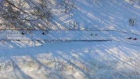 Antenne des sportifs courant sur le pont couvert par neige en fer en parc de ville en hiver banque de vidéos