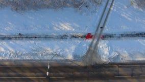 Antenne des sportifs pulsant sur le chemin neigeux près de la route urbaine en hiver banque de vidéos