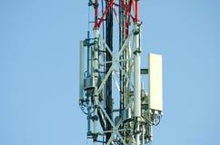 Antenne di telecomunicazione all'aperto sulla fine alta della costruzione del palo del metallo rosso e bianco su Fotografia Stock