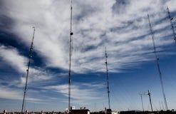 Antenne di telecomunicazioni su un cielo blu nuvoloso Fotografia Stock