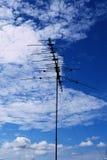 Antenne di televisioni con il fondo nuvoloso del cielo blu Immagine Stock