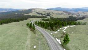 Antenne die geschotene Twee auto's spinnen die op de weg zich één voor één in de bergen bewegen stock video