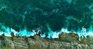 Antenne: Die Meereswellen brechen gegen die Felsen auf dem Ufer stock footage
