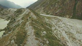 Antenne die van de de vliegende pieken en rivier van de hommelberg schieten De vallei van de berg stock videobeelden