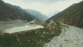 Antenne die van het vliegende meer en de pieken van de hommel mooie berg schieten stock video