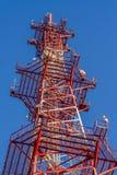 Antenne du bâtiment de communication et du ciel bleu Image libre de droits