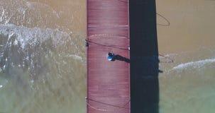 Antenne: Een Aziatisch meisje loopt op een pijler naar het strand met palmen stock video