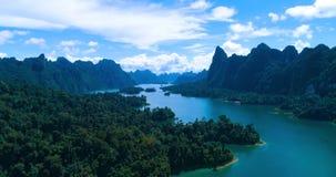 Antenne: Een meer onder de bergen en de wildernis met een bewolkte blauwe hemel stock video