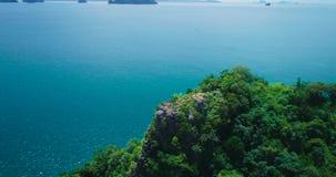 Antenne: Een meisje bevindt zich bovenop een berg op het eiland en de golven haar handen stock footage