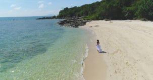 Antenne: Een meisje in een witte kleding loopt langs het strand door het water stock footage