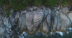 Antenne: Een mens bevindt zich alleen op een klip dichtbij het overzees en stelt emotioneel stock footage