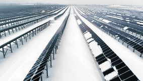 ANTENNE: Foto-voltaisch im Winter umfasst mit Schnee Sonnenkollektoren unter den Schneeantrieben, umfasst mit Schnee alternative stock footage