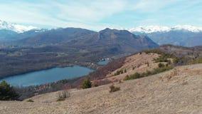 Antenne: hommelpanning over bosvalleimeer, luchtmening van sneeuw afgedekte bergketen op de Alpen, duidelijke blauwe hemel, Turij stock videobeelden