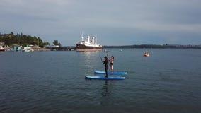 ANTENNE : Jeunes couples et une réunion d'ami sur des panneaux de PETITE GORGÉE sur le lac saigné banque de vidéos