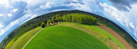 Antenne kurvte breiten Panoramablick auf ländlicher Landschaft mit Haus, Wald, Wolken und Feldern lizenzfreies stockbild