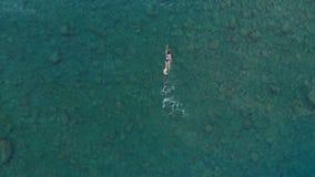 ANTENNE : la femme flottant sur la surface de l'eau bleue, nageant en mer Méditerranée transparente, dessus regardent vers le bas Photo stock