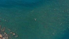 ANTENNE : la femme flottant sur la surface de l'eau bleue, nageant en mer Méditerranée transparente, dessus regardent vers le bas Photos stock