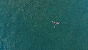 ANTENNE : la femme flottant sur la surface de l'eau bleue, nageant en mer Méditerranée transparente, dessus regardent vers le bas Photographie stock