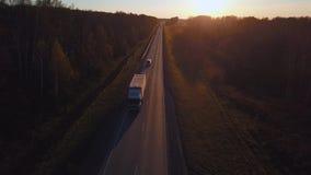 Antenne : la voiture avec le récipient monte sur la route au coucher du soleil Le camion monte la route banque de vidéos