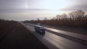 Antenne: leveringsvrachtwagens die naar de zon drijven de auto met de containerritten op de weg aan de zonsondergang Vrachtwagenr stock videobeelden