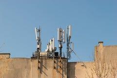 Antenne mobile sur le toit d'un bâtiment contre le ciel bleu Communicateurs de radiodiffusion et de réseau, récepteurs Téléphone  Photos libres de droits